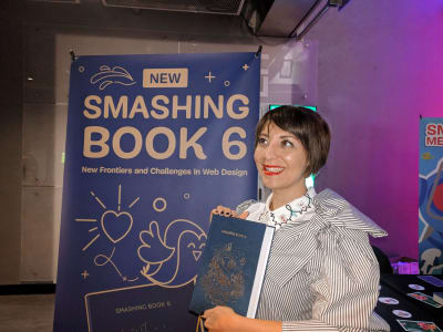 Cover designer Chiara Aliotta holding Smashing Book 6 in her hand in front of the Smashing books stand at SmashingConf NY