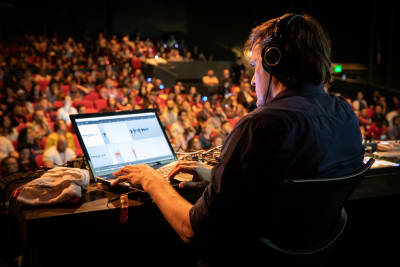 Photo of DJ Tobi Lessnow on stage with the crowd watching