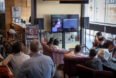 People on sofas watching a presentation via a live stream